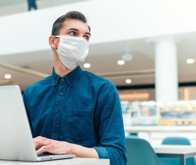 閉じる。空のオフィスでラップトップに取り組んでいるビジネスマン。健康保護の概念