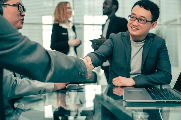 확대. 비즈니스 파트너는 확고한 악수로 거래를 확인합니다. 협력의 개념