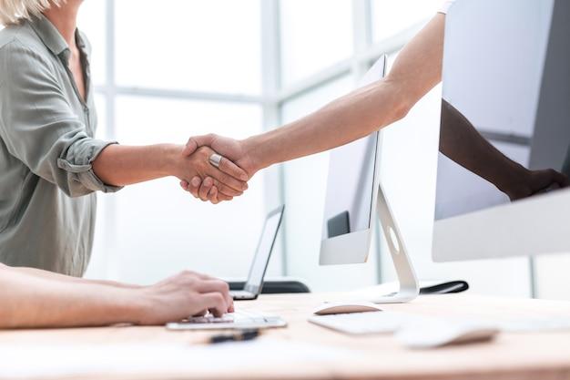 閉じる。ビジネスパートナーはオフィスで握手します。ビジネスコンセプト