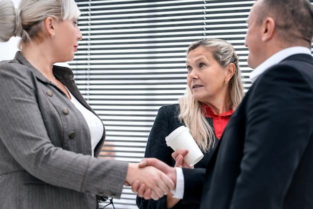 Закройте вверх. деловые партнеры, пожимая руки на встрече в офисе. бизнес-концепция