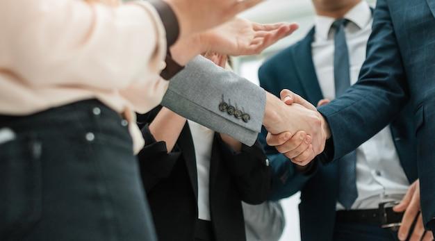 Крупным планом деловые партнеры, пожимая руки в офисе
