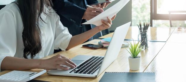 Закройте деловых людей, обсуждающих диаграммы и графики, показывающие результаты их успешной совместной работы.
