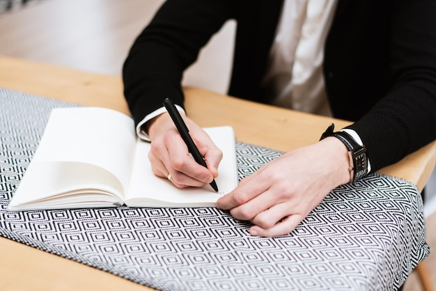 Close up of business people hand in suit writing on notebook or document. workspace of a young office worker