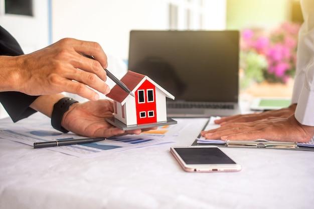 クローズアップビジネスの人々は家の建物の概念を手渡します
