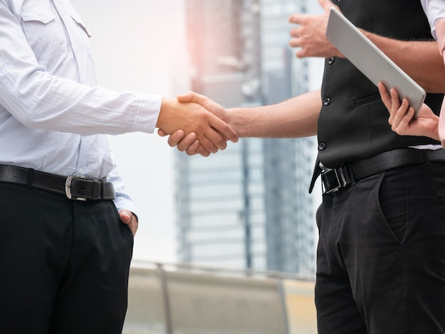 Close-up of business people handshaking on city background. business partnership outdoor meeting