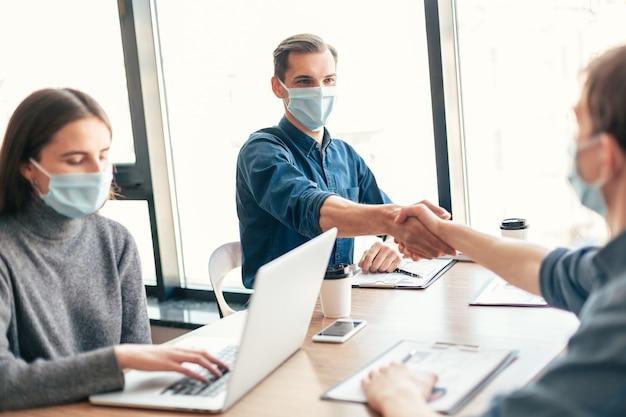 확대. 서로 악수하는 보호 마스크에 사업 사람들. 건강 보호의 개념.