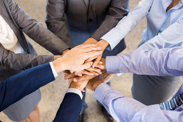 Close-up of business people stacking hands in meeting at office