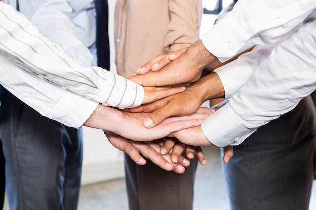 Close-up of business people stacking hands in office