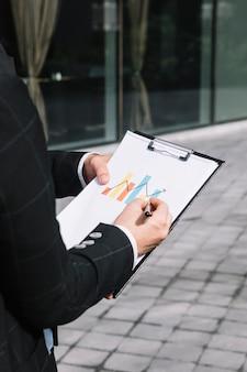 Primo piano della mano della persona di affari che disegna freccia crescente sul grafico sopra la lavagna per appunti