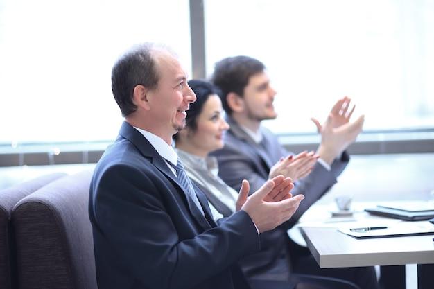 Закройте вверх. бизнес-команда аплодирует спикеру, сидя на рабочем месте.