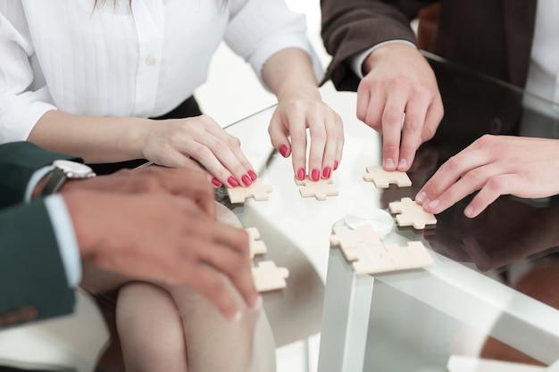 Close up business team assembling puzzle pieces