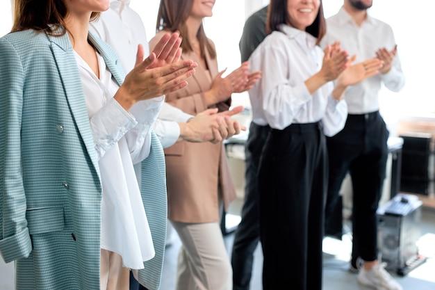 明るいモダンなオフィスで、手をたたくクローズアップビジネスチーム、若い男性と女性の成功した仕事。会った後、職場で、一緒に立っているフォーマルな服を着た美しい若い女性と男性