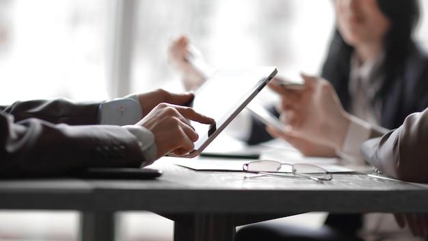 Close up. бизнес-команда обсуждает новые идеи в офисе. люди и технологии
