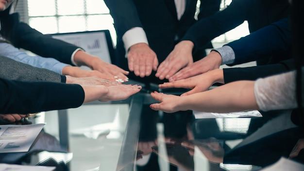 확대. 책상 위의 손바닥에 비즈니스 팀이 합류했습니다. 팀워크의 개념