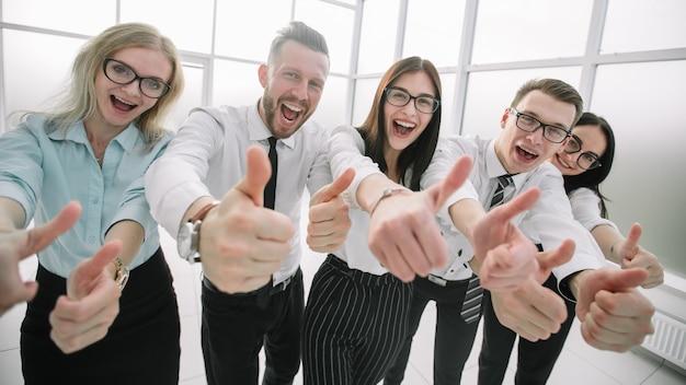 Закройте вверх. бизнес-команда показывает палец вверх. концепция успеха