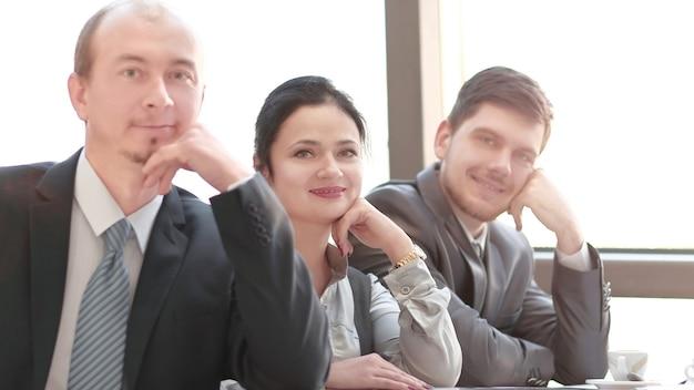 Закройте вверх. бизнес-команда, сидя за своим столом на встрече