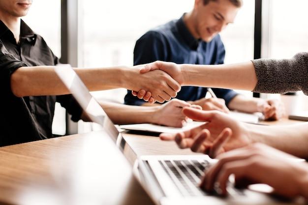 Крупным планом бизнес-команда работает, сидя за офисным столом
