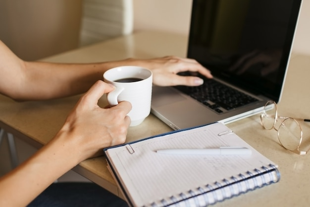 Close up business woman checking daily news in laptop in the kitchen while drinking morning coffee.