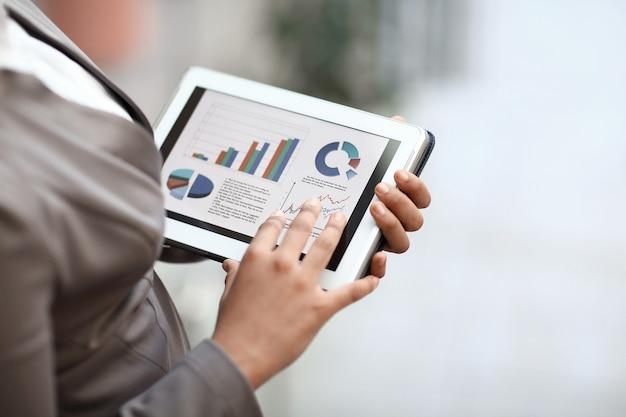확대. 비즈니스 우먼 디지털 태블릿을 사용 하여 재무 보고서를 확인합니다.