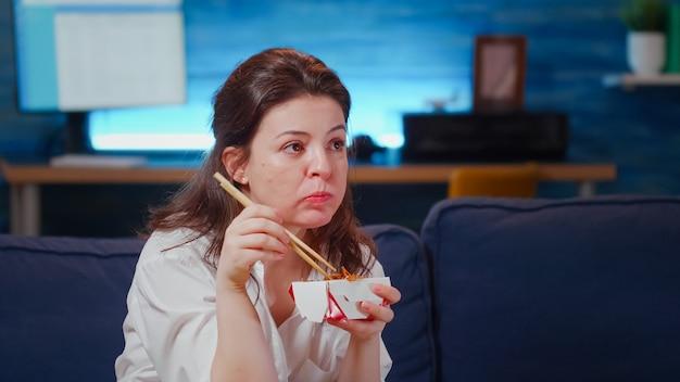 Primo piano di una donna d'affari che mangia cibo asiatico alla tv?