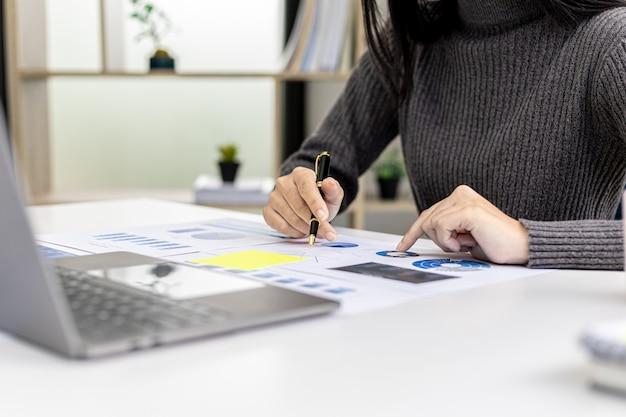 펜을 들고 회사 재무 문서의 막대 차트를 가리키는 클로즈업 비즈니스 여성은 회사 성장 방법을 계획하기 위해 과거 재무 데이터를 분석하고 있습니다. 금융 개념입니다.