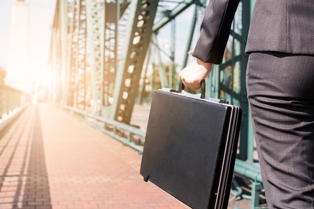 Close up business woman holding black briefcase on the metal bridge walking to work
