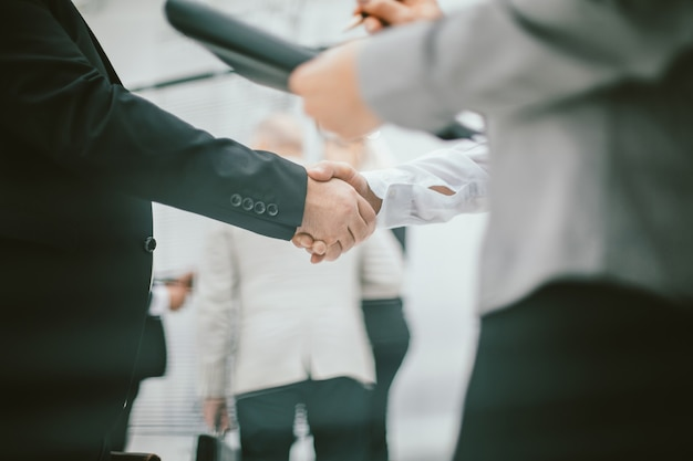 Крупным планом деловая женщина встречает коллегу рукопожатием