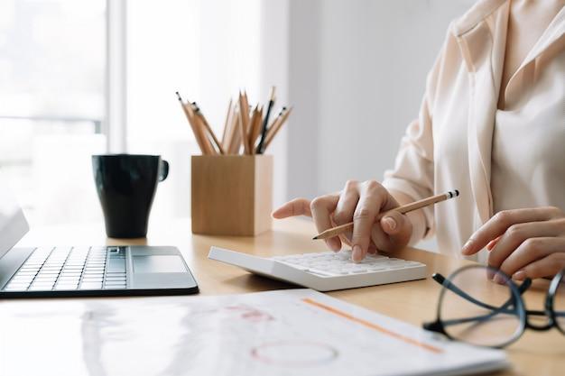 Крупным планом бизнес-леди или бухгалтер с помощью калькулятора с компьютерным ноутбуком