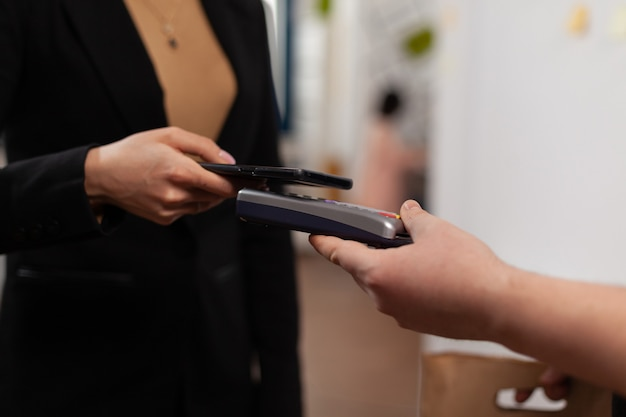 Close up of business woman paying delivery guy from frood service, using smartphone nfc technology