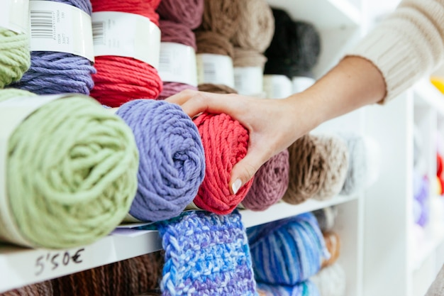 Close up of a business woman picking up a pink wool yarn