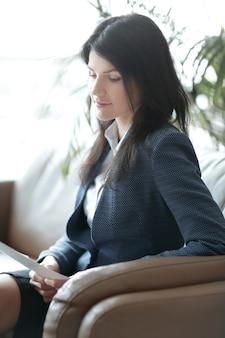 Крупным планом деловая женщина, читающая деловой документ, сидя в кресле