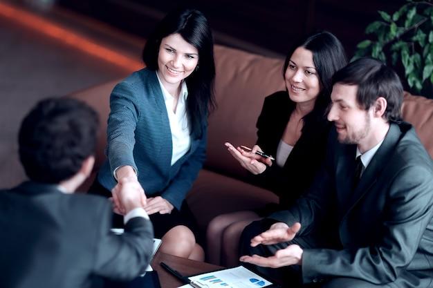 クローズアップ。仕事机に座っているビジネスパートナーと握手するビジネスウーマン