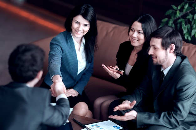 Close up.business woman shaking hands with business partner sitting at work desk