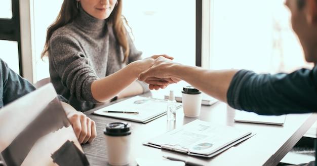 彼女の金融パートナーのビジネスコンセプトと握手するビジネス女性をクローズアップ