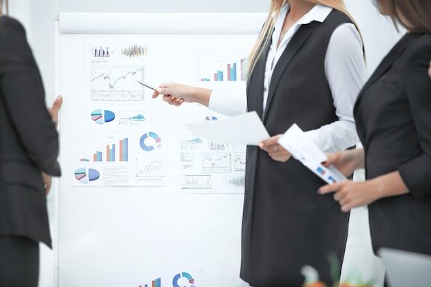財務データとフリップチャートにペンを表示しているビジネスウーマンをクローズアップ