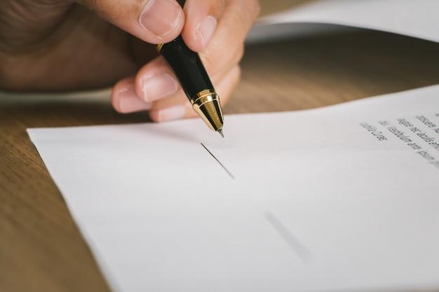 Закройте деловая женщина, подписав условия договора документ на деревянный стол
