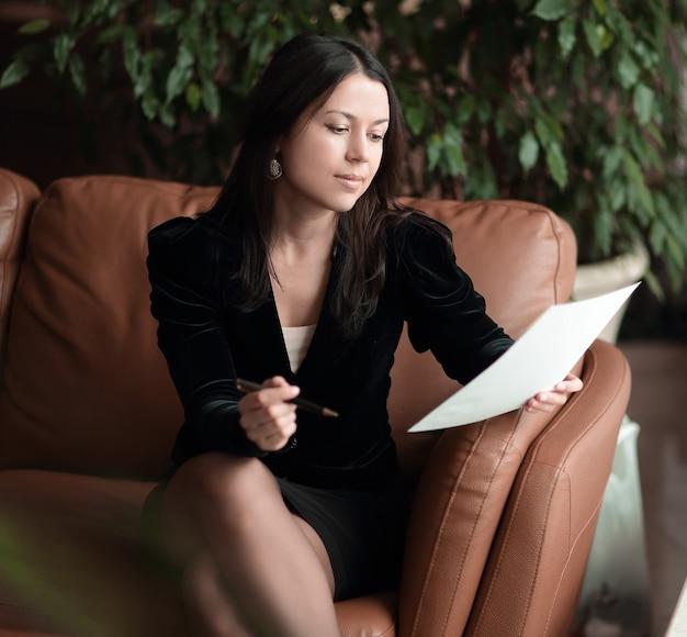 Крупным планом деловая женщина, сидящая в бизнес-центре и читающая документы