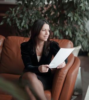 Закройте вверх. деловая женщина сидит в бизнес-центре и читает документы