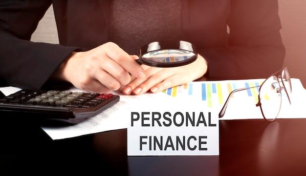 Крупным планом деловая женщина с помощью калькулятора и диаграмм делает математические финансы на деревянном столе в офисе и бизнес рабочий фон с текстом личные финансы