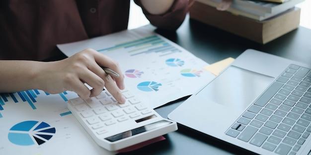 電卓を使ってオフィスの木の机の上のグラフをチェックするビジネスウーマンの接写
