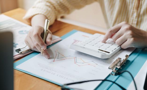 計算機とラップトップを使用してビジネスウーマンをクローズアップオフィスの木製の机で数学の財務を行うために、ビジネスの背景税会計統計と分析研究の概念