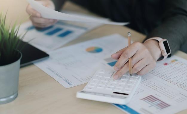 Крупным планом деловая женщина, использующая калькулятор и ноутбук для математических финансов на деревянном столе в офисе и бизнес, рабочий фон, налоги, бухгалтерский учет, статистика и концепция аналитических исследований