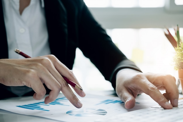Закройте вверх по бизнес-леди используя калькулятор и компьтер-книжку для финансов математики на деревянном столе в концепции деятельности офиса, дела, налога, бухгалтерии, статистики и аналитических исследований
