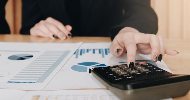 計算機とラップトップを使用してビジネスウーマンをクローズアップオフィスやビジネスの仕事、税務、会計、統計、分析研究の概念の木製の机の上で数学の金融を行う