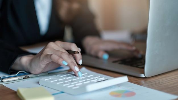 나무 책상, 세금, 회계, 통계 및 분석 연구 개념에 대한 수학 재무를 위해 계산기와 노트북을 사용하는 비즈니스 여성을 마감합니다.