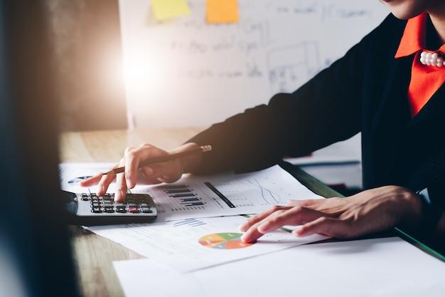 クローズアップビジネスの女性のための計算機を使用してオフィスで木製の机の上で数学金融を行う