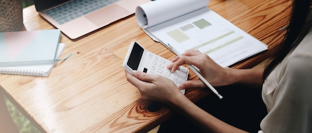 Close up business woman using calculator and laptop for do math finance on wooden desk in office and business working background, tax, accounting, statistics and analytic research concept