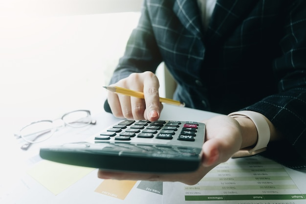 Close up business woman using calculator for do math finance on wooden desk in office