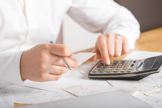 Close up of businessman or accountant hand holding pen working on calculator accountancy document and laptop computer at office, business concept