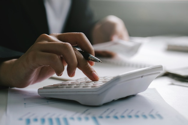 Close up of businessman or accountant hand holding pen working on calculator to calculate business data,finance accounting concept